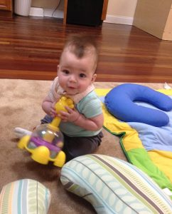 Elliot playing with a yellow toy at daycare and holding it in both hands.