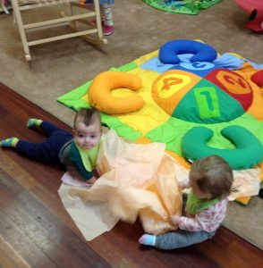 Elliot and another baby playing with tissue paper at daycare.
